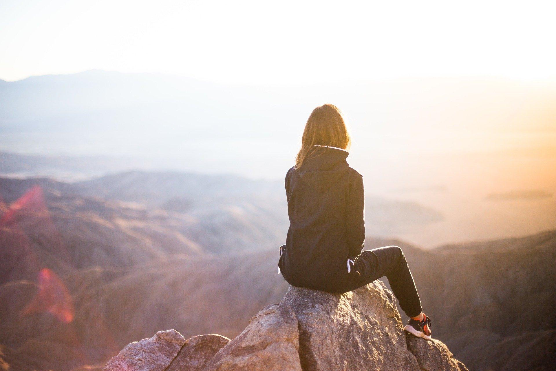 pige på toppen af et bjerg